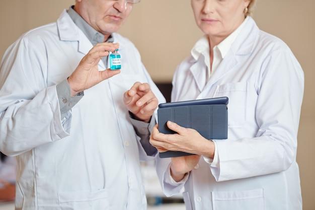 Image recadrée de travailleurs médicaux avec l'article de lecture du vaccin covid-19 sur tablette