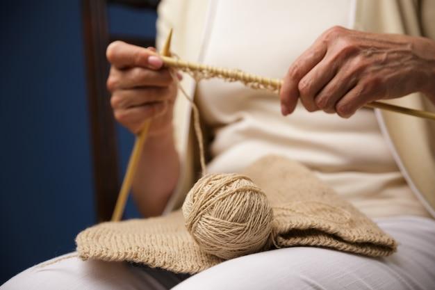 Image recadrée de vieille femme à tricoter.