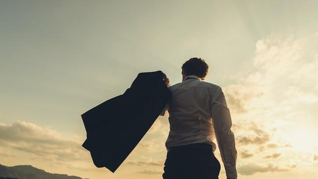 Image rétro d'un jeune homme d'affaires prospère, debout sous un ciel du soir glorieux, balançant avec confiance sa veste par-dessus son épaule.