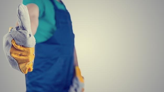 Image rétro d'un ouvrier portant des gants de protection et des combinaisons donnant un geste d'approbation, de réussite et de motivation, vue rapprochée de la main avec fond.