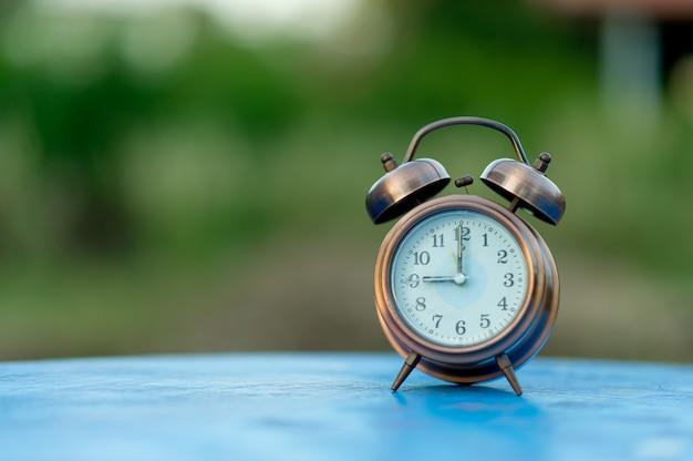 Image de réveil doré placé sur une table bleue