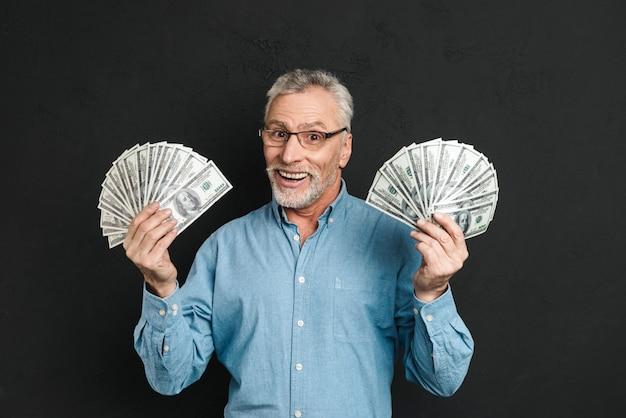 Image de riche homme adulte heureux des années 60 aux cheveux gris tenant de l'argent deux fans de billets de 100 dollars et se réjouissant de sa richesse, isolé sur mur noir