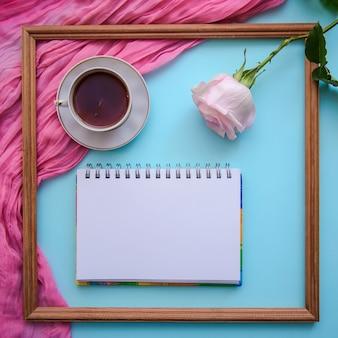 Image romantique avec cadre en bois, thé, bloc-notes et rose