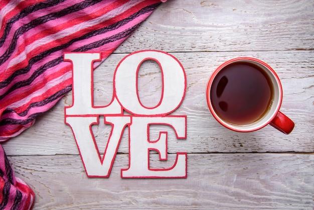Image romantique simple et mignonne avec une tasse de thé et le mot love sur un fond en bois pour la saint-valentin
