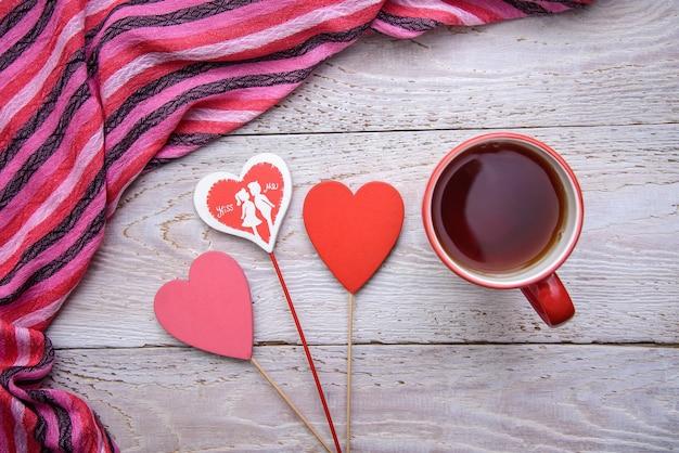 Image romantique simple et mignonne avec une tasse de thé et trois coeurs sur un fond en bois pour la saint-valentin