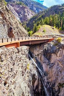 Image de la route au-dessus de la cascade vers le bas de la grande montagne de roche grise