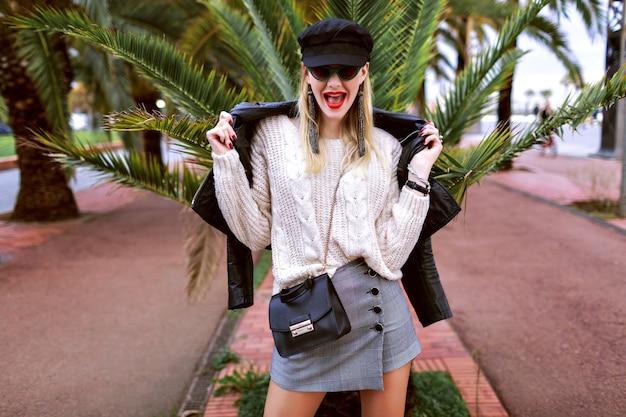 Image de rue de mode du modèle avec de longues jambes portant une tenue élégante glamour, printemps, humeur de voyage, palmiers autour, baskets, casquette, veste en cuir, mini-jupe, pull, accessoires et bijoux.