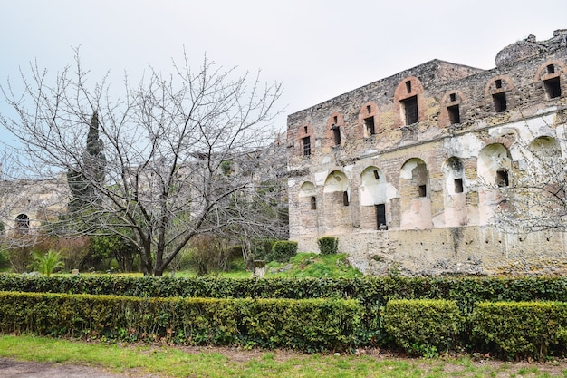 Image d'une ruine avec des haies au premier plan sous un ciel nuageux
