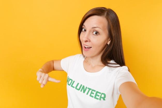 Image selfie d'une femme heureuse souriante et satisfaite en t-shirt blanc avec inscription écrite bénévole titre vert isolé sur fond jaune. aide d'assistance gratuite volontaire, concept de travail de grâce de charité.