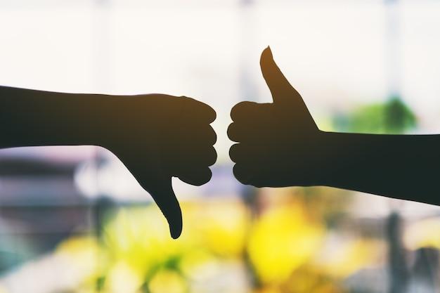 Image silhouette de deux mains faisant signe de pouce vers le haut et le pouce vers le bas