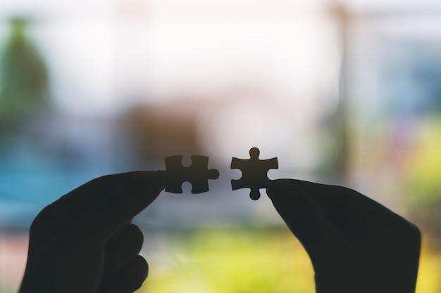 Image silhouette de deux mains tenant et assemblant un morceau de puzzle blanc
