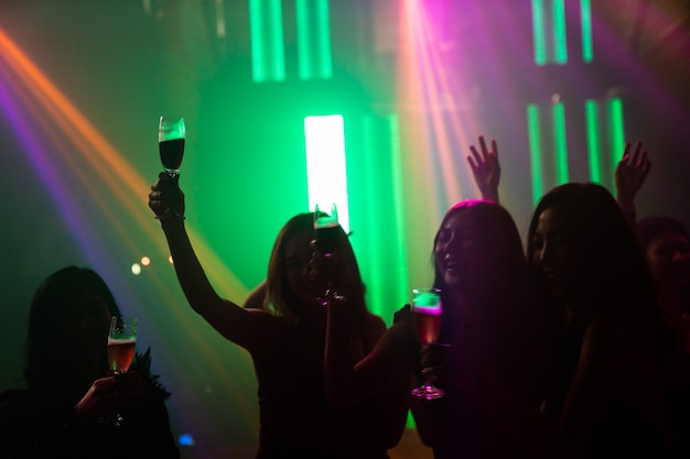 Image de la silhouette des gens dansent en discothèque sur la musique du dj sur scène