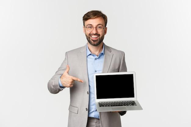 Image de sourire bel homme d'affaires en costume gris et lunettes, pointer du doigt sur l'ordinateur portable