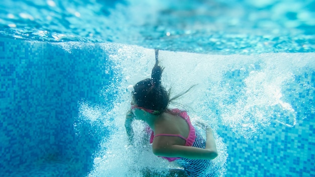 Image sous-marine d'une adolescente en maillot de bain rayé plongeant et nageant sous l'eau à la piscine