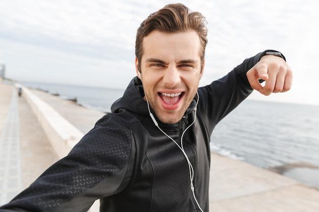 Image d'un sportif amusant de 30 ans en vêtements de sport noirs et écouteurs, prenant une photo de selfie sur un téléphone mobile tout en marchant au bord de la mer