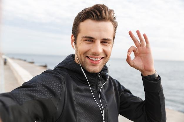 Image d'un sportif satisfait des années 30 en vêtements de sport noirs et écouteurs, prenant une photo de selfie sur un téléphone mobile tout en marchant au bord de la mer