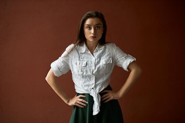 Image studio de l'élégante jeune femme de race blanche confiante en jupe et chemise blanche posant isolé avec les mains sur sa taille, exprimant son désaccord, étant réticent