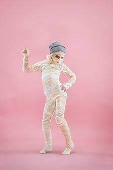 Image studio d'une jeune adolescente bandée sur fond rose bloody halloween theme
