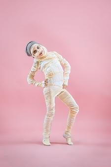 Image studio d'une jeune adolescente bandée, sur fond rose. thème d'halloween sanglant : le fond de studio de maniaque fou