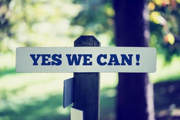 Image de style instagram rétro d'un vieux panneau rustique avec la phrase oui, nous pouvons, à l'extérieur dans les bois ensoleillés.