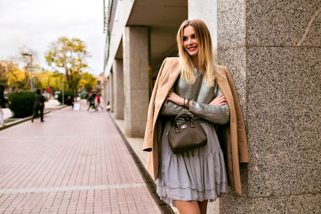 Image de style de rue de mode d'une femme élégante blonde, vêtue d'une robe en soie de luxe, d'un pull à la mode, d'un manteau en cachemire et d'un sac en cuir, des couleurs douces et chaudes, une ambiance printemps automne mi-saison.
