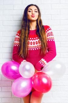 Image de style de vie intérieur d'une jolie fille brune drôle avec un maquillage lumineux et des cheveux longs, portant un pull à la mode et tenant des ballons de fête roses.
