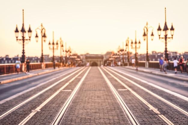 Image de style vintage de rue floue avec des lumières colorées en soirée au pont de pierre, bordeaux, france