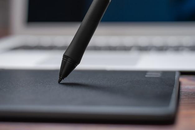 Image d'une tablette graphique, d'un stylet et d'un ordinateur portable sur une table en bois. lieu de travail de concepteur.