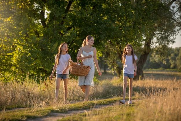Image tonique de famille heureuse marchant au pré pour pique-niquer