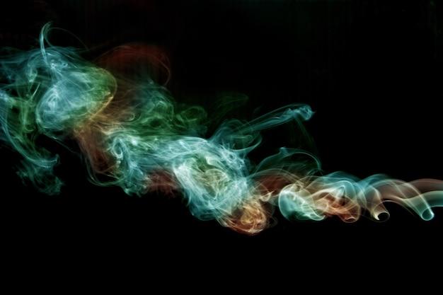 Image de torsion de fumée verte et orange sur fond noir