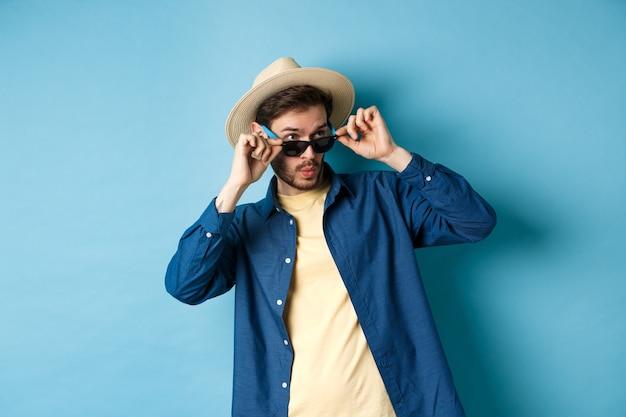 Image d'un touriste vérifiant quelque chose de cool, des lunettes de soleil à décoller, dites wow et regardant de côté impressionné, debout sur fond bleu.
