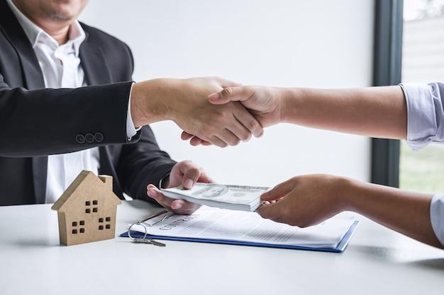 Image d'une transaction immobilière réussie, d'un courtier et d'un client se serrant la main après avoir signé un formulaire de demande approuvé par contrat, concernant une offre de prêt hypothécaire et une assurance habitation.