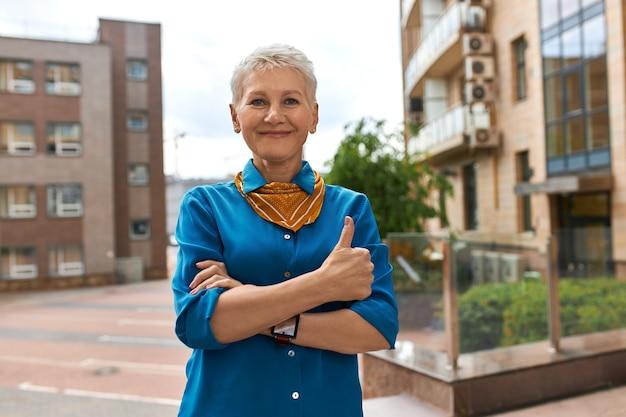 Image urbaine en plein air de femme mature réussie confiante dans des vêtements élégants posant sur une rue vide avec un bâtiment moderne de plusieurs étages en arrière-plan, ayant un regard positif, faisant le geste de pouce en l'air