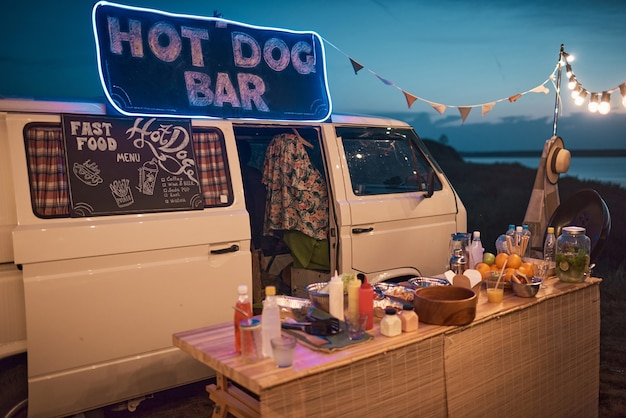 Image d'un van avec un bar à hot-dogs avec de la nourriture et des boissons à la fête sur la plage