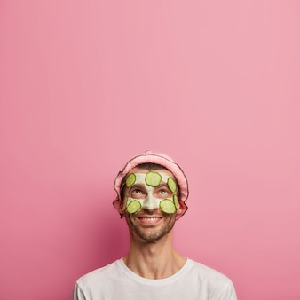 Image verticale de bel homme heureux applique des tranches de concombre, porte un chapeau de bain, bénéficie de soins de beauté