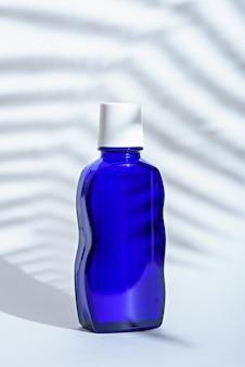 Image verticale de la bouteille cosmétique en verre bleu classique sur fond blanc