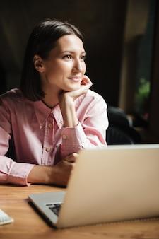 Image verticale de femme brune souriante assise près de la table