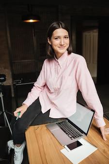 Image verticale de femme brune souriante assise sur table