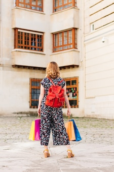 Image verticale d'une femme de dos avec des sacs colorés dans les mains, lors de ses achats en solde.