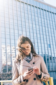 Image verticale de la jeune femme brune en manteau beige regardant un téléphone portable sur un immeuble de grande hauteur