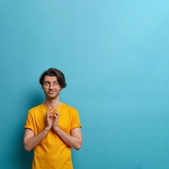 Image verticale d'un mec réfléchi sournois steepls doigts, réfléchit à un excellent plan, organise quelque chose, a une bonne idée, une mauvaise intention, sait comment mieux agir, habillé avec désinvolture, isolé sur mur bleu