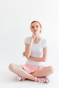Image verticale de pensive ginger girl sitting on the floor and looking up