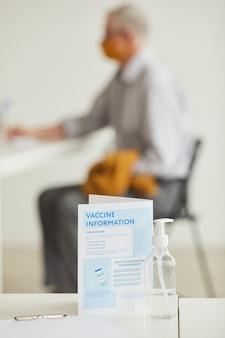 Image verticale d'un signe de vaccination contre le covid dans une clinique avec un homme âgé se faisant vacciner en arrière-plan, espace pour copie