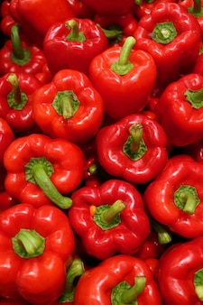 Image verticale de tas de poivrons rouges mûrs frais avec tige verte