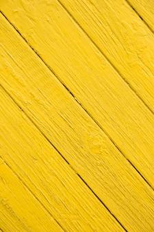 Image verticale de vieilles planches diagonales avec peinture jaune vif.