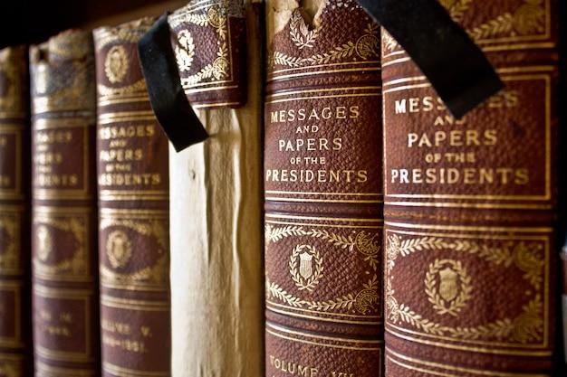 Image de vieux livres reliés avec du tissu alignés sur une étagère