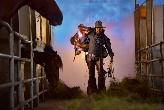 Une image vintage d'un cowboy portant une selle dans son écurie.