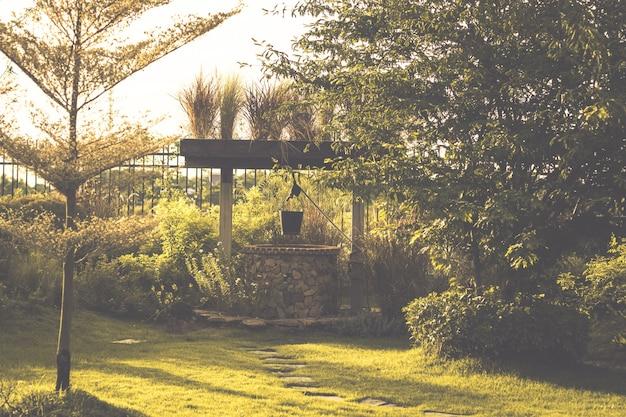 Image vintage du jardin de campagne avec puits d'eau dans un village rustique