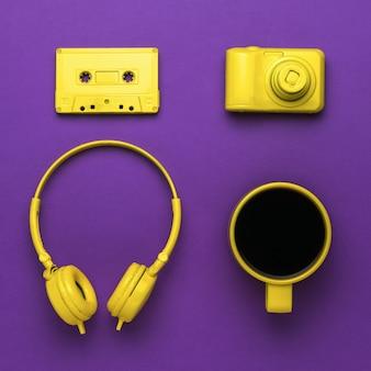 Image vintage d'une tasse à café et d'accessoires jaunes élégants sur fond violet. tendance de couleur.