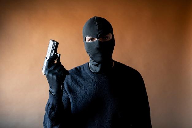 Image d'un voleur avec cagoule et arme à la main